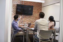 Businesspeople In Meeting Room Looking At Screen Stock Image