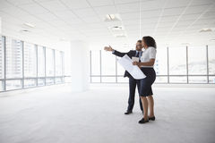 Businesspeople Meeting To Look At Plans In Empty Office stock image
