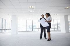 Businesspeople Meeting To Look At Plans In Empty Office Stock Images