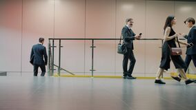Businesspeople in formalwear moving in office building hall using gadgets rolling suitcase