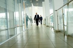 Businesspeople on the move. Businesspeople going along corridor inside office building royalty free stock photography