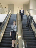Businesspeople Moving Down On Escalator In Office Royalty Free Stock Image