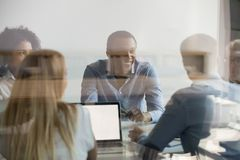 Businesspeople negotiating at boardroom view through glass wall. Diverse businesspeople company boss and corporation members discussing planning talking during stock images