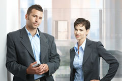 Businesspeople in office. Two young businesspeople standing in modern office with glass walls, looking at camera, smiling Royalty Free Stock Photo