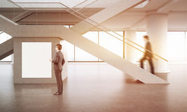 Businesspeople in office lobby with poster. Stock Images