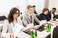Businesspeople with papers at conference Stock Photo