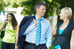 Businesspeople in park. Young businesspeople talking in downtown park royalty free stock image