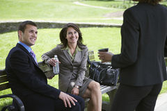 Businesspeople On Park Bench Looks At Colleague Stock Photos
