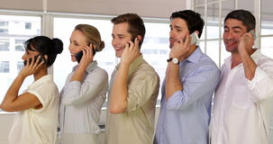 Businesspeople phoning while standing in a row Royalty Free Stock Photos