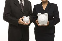 Businesspeople with piggybanks. Caucasian middle-aged businessman and Filipino businesswoman holding different sized piggybanks Stock Photo