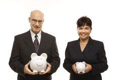 Businesspeople with piggybanks. Caucasian middle-aged businessman and Filipino businesswoman holding different sized piggybanks Stock Photos