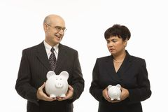 Businesspeople with piggybanks. Caucasian middle-aged businessman and Filipino businesswoman holding different sized piggybanks royalty free stock photo