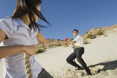 Businesspeople Playing Tug Of War. Two business people playing tug of war in the desert Royalty Free Stock Photo