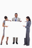 Businesspeople pointing and looking at blank sign Royalty Free Stock Photo