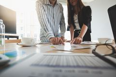 Businesspeople poiting at document on table. Businesswomen and freelance worker poiting at data report paper on table in meeting room. Startup business teamwork Stock Photos