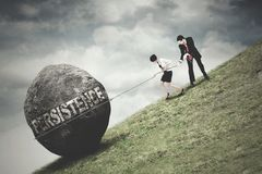 Businesspeople pull a boulder with Persistence text. Persistence Concept. Two young businesspeople pull up a boulder with a chain and Persistence text on the Royalty Free Stock Photos