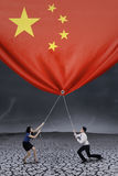 Businesspeople pulling down a chinese flag Royalty Free Stock Photos