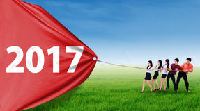 Businesspeople pulling number 2017. Group of young businesspeople pulling number 2017 on a red banner, shot outdoors on the meadow Royalty Free Stock Image