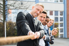 Businesspeople Pulling Rope. Group Of Multiethnic Businesspeople Pulling Rope Playing Tug Of War stock photo