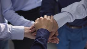 Businesspeople putting their hands on top of each other, team building support stock footage