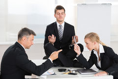 Businesspeople Quarreling In Front Of Businessman Meditating Stock Images