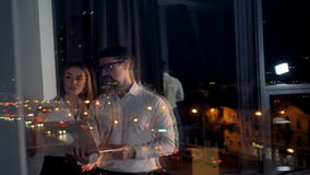 Businesspeople reflect in an office window as they discuss work. A talking businesswoman and a businessman reflect in a dark evening window stock footage