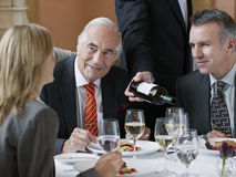 Businesspeople At Restaurant Table As Waiter Serves Wine. Three businesspeople talking at restaurant table as waiter serves wine stock photos
