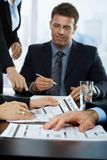 Businesspeople reviewing business report. Focus on hand in middle stock image