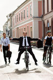 Businesspeople riding on bikes and running Stock Photography