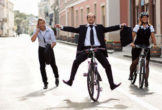 Businesspeople riding on bikes and running Royalty Free Stock Photo