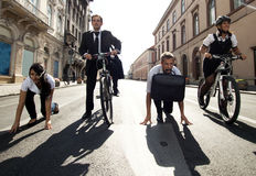 Businesspeople riding on bikes and running Stock Photo