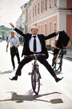 Businesspeople riding on bikes and running Stock Image