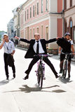 Businesspeople riding on bikes and running Royalty Free Stock Photos