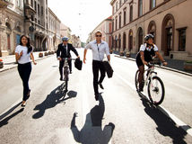 Businesspeople riding on bikes and running Stock Photos