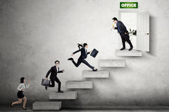 Businesspeople running to enter the office. Group of young businesspeople compete on the stair by running toward the office door Royalty Free Stock Image