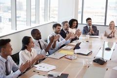 Businesspeople runt om styrelsetabellen applåderar presentation arkivbild