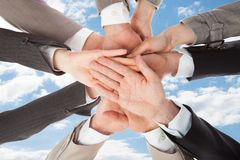 Businesspeople's hands on top of each other symbolizing unity Stock Photos