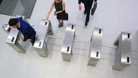 Businesspeople scanning their cards at turnstile gate stock video footage