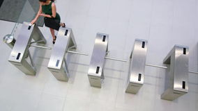 Businesspeople scanning their cards at turnstile gate. In office stock footage