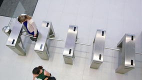 Businesspeople scanning their cards at turnstile gate. In office stock video footage