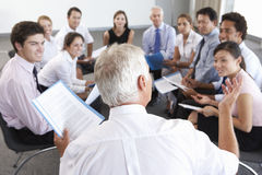 Businesspeople Seated In Circle At Company Seminar Stock Image