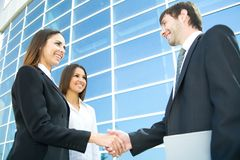Businesspeople shake hands. Young and successful businesspeople shake hands against the modern office building Royalty Free Stock Photos