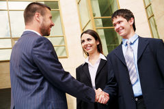 Businesspeople shake hands. Young and successful businesspeople shake hands against the modern office building stock photo