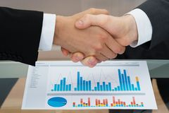 Businesspeople shaking hand in front of graph Stock Images