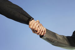 Businesspeople shaking hands against clear sky Royalty Free Stock Photo