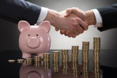 Businesspeople shaking hands with coins and piggybank Royalty Free Stock Image