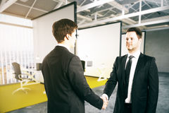 Businesspeople shaking hands. European businessmen shaking hands in modern business interior. Partnership concept. 3D Rendering Royalty Free Stock Photos
