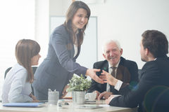 Businesspeople shaking hands. Image of businesspeople shaking hands during business meeting stock photo