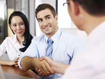 Businesspeople shaking hands before meeting. A caucasion businessman shaking hands with his asian partner before meeting Royalty Free Stock Photo