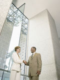 Businesspeople Shaking Hands In Office Building Stock Photo